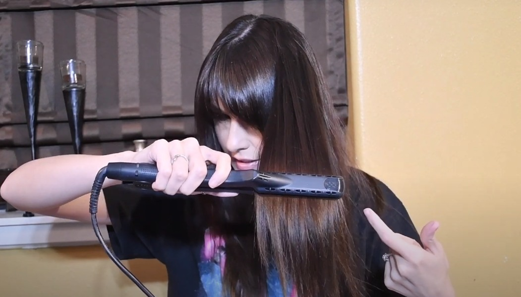 girl straightening her hair with the croc flat iron